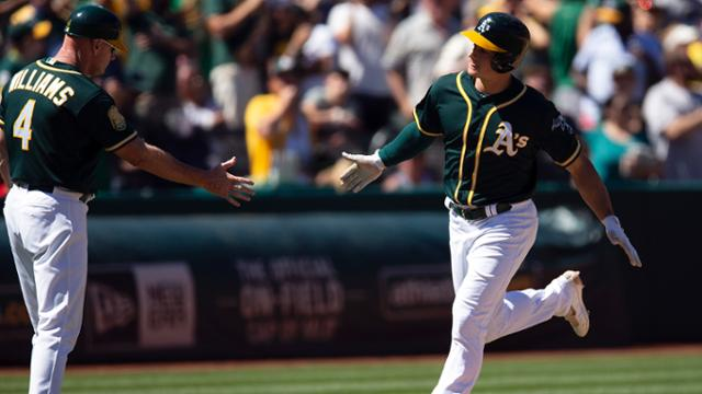 Oakland Athletics' Matt Chapman is congratulated by third base coach Matt Williams for his two-run home run against the Detroit Tigers during the seventh inning of a baseball game, Sunday, Aug. 5, 2018, in Oakland, Calif. The A's won 6-0. (AP Photo/D. Ross Cameron)