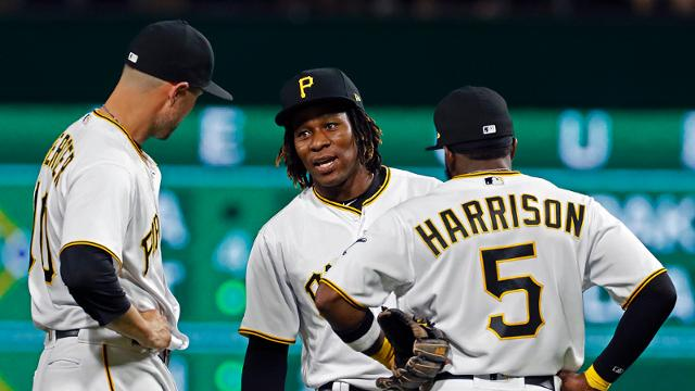 Pittsburgh Pirates' Gift Ngoepe (61) a native of South Africa, and the first baseball player from the continent of Africa to play in the Major Leagues, center, talks with Jordy Mercer, left, and Josh Harrison (5) as he takes the field for the first time in the Major Leagues, as part of a fourth inning double switch during a baseball game against the Chicago Cubs in Pittsburgh, Wednesday, April 26, 2017. (AP Photo/Gene J. Puskar)