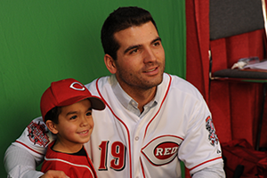 Joey Votto posing for a photo with a young Reds fan