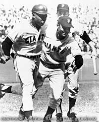 Felipe Alou (right) welcomes Willie Mays home after the slugger hit a homer against the Dodgers in a 1962 playoff.