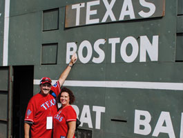 A couple poses in front of the Green Monster