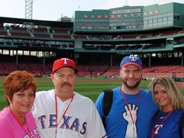 A family poses for a photo from the field at iconic Fenway Park