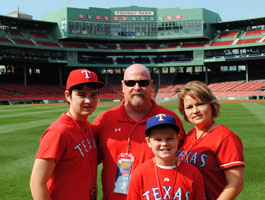 A family poses for a photo in Center Field at Fenway Park