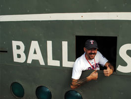 A fan strikes a pose from inside the Green Monster